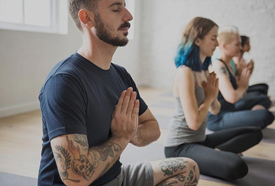 men and woman performing self care meditation yoga